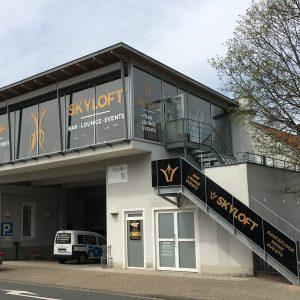 Gesamtansicht des Skylofts mit Fensterbeklebung und mit Platten verkleideter Eingangstreppe