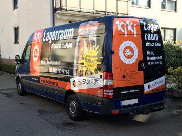 Schrägansicht eines dunkelblauen Lieferwagens mit neuer Fahrzeugfolierung für KiKii Umzüge