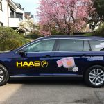 Seitenansicht eines dunkelblauen Passats mit neuer Fahrzeugbeschriftung für die Firma Haas