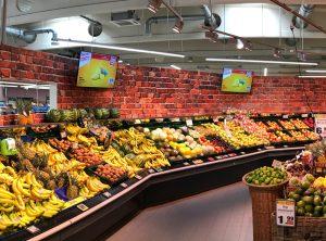 Obst- und Gemüseregale mit einer frisch folierten Wand in Backsteinoptik im Edeka Stengel