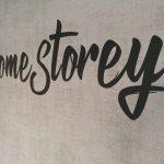 Wandtattoo - Nahaufnahme des Home Storey Wandtattoos in schwarzmatt auf einer grauen Tapete