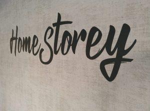 Nahaufnahme des Home Storey Wandtattoos in schwarzmatt auf einer grauen Tapete