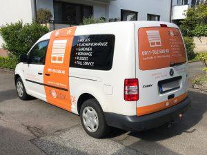 Auffällige orangefarbene Fahrzeugbeklebung auf weißem Caddy für die Firma Rollox