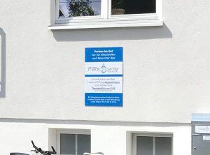 Nahaufnahme eines Parkplatzschildes im Innenhof der Arztpraxis Medic Center