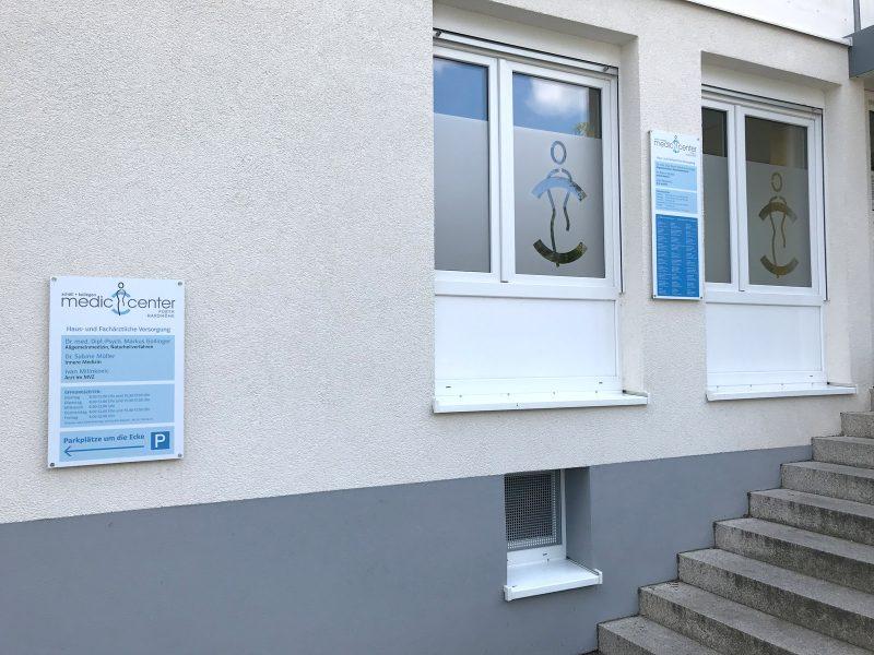 Sichtschutzfolierung mit ausgeschnittenem Logo aus Glasdekorfolie für zwei Fenster und entspprechender Beschilderung an der Fassade einer Medic Center Praxis