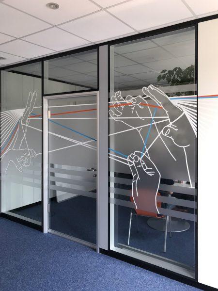 Auffallender Sichtschutz - Sichtschutzfolierung aus Milchglasfolie mit darauf geklebten farbigem Muster auf einer Glasfront in Büroräumlichkeiten der Firma isyst