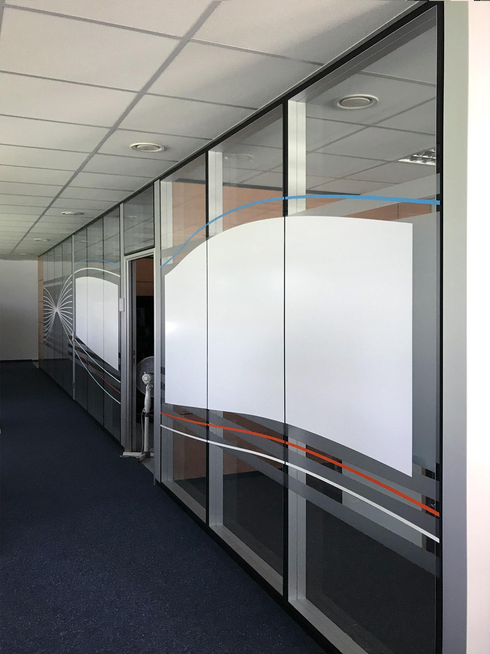 Sichtschutzfolierung aus Milchglasfolie mit darauf geklebten farbigem Muster und teilweise Whiteboardfolie auf einer Glasfront in Büroräumlichkeiten der Firma isyst