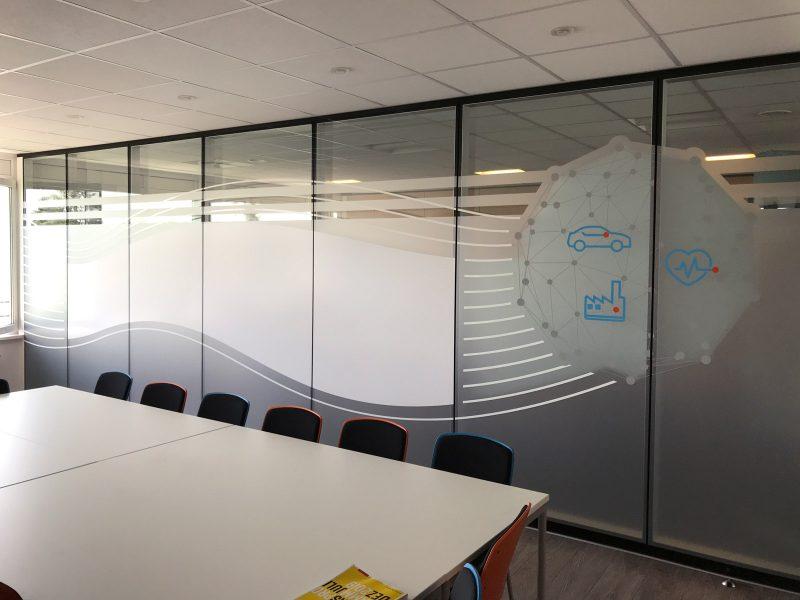 Sichtschutzfolierung aus Milchglasfolie mit darauf geklebten farbigem Muster und Whiteboardfolie auf einer Glasfront in Büroräumlichkeiten der Firma isyst