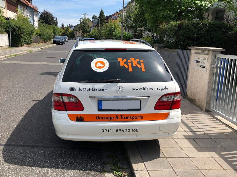 Heckansicht eines weißen Mercedes Combi mit neuer Folienbeschriftung für KiKi Umzüge