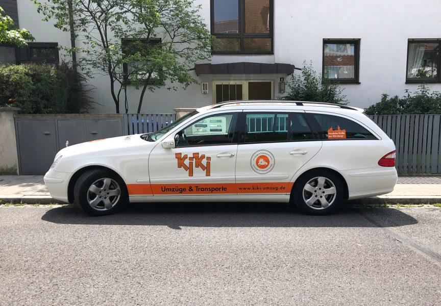 Seitenansicht eines weißen Mercedes Combi mit neuer Folienbeschriftung für KiKi Umzüge