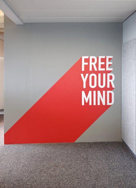 Rot-weißes Wandtattoo mit dem Spruch FREE YOUR MIND bei Design Offices
