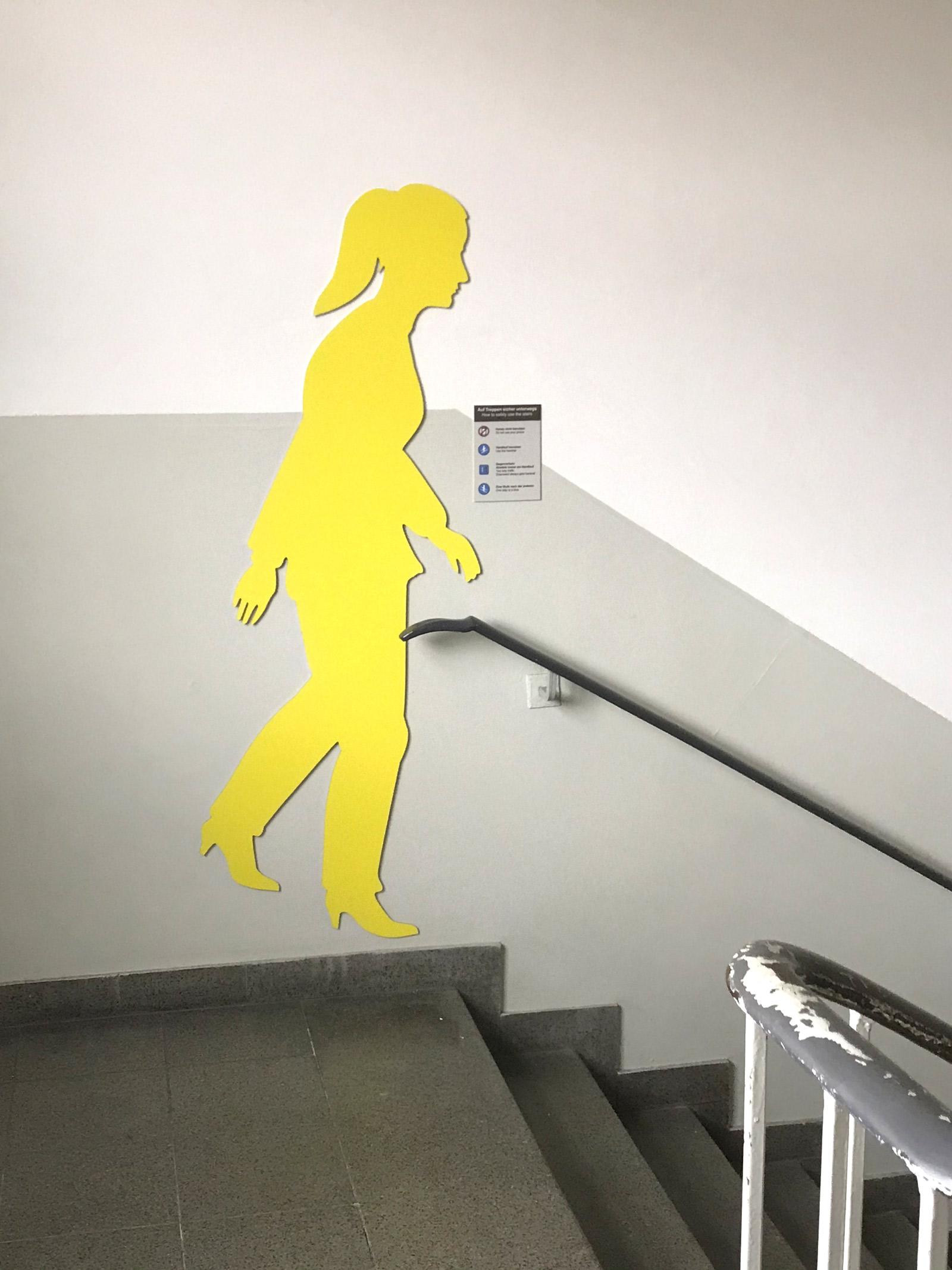 Gelbe weibliche Schattenfigur in einem Treppenhaus an der Wand