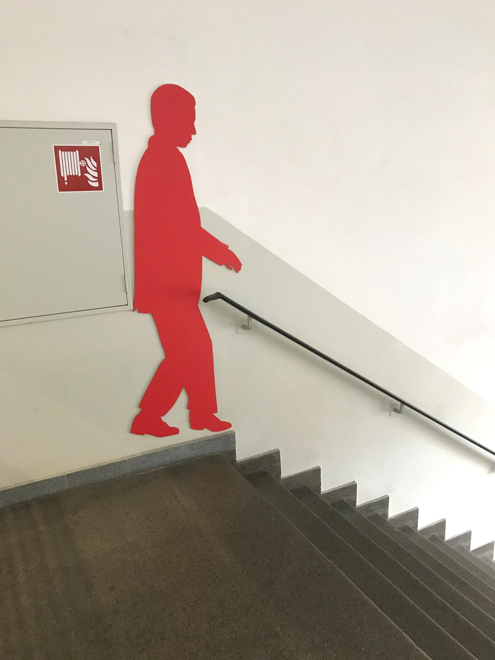 Rote männliche Schattenfigur in einem Treppenhaus an der Wand
