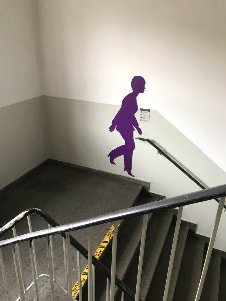 Violette weibliche Schattenfigur in einem Treppenhaus an der Wand
