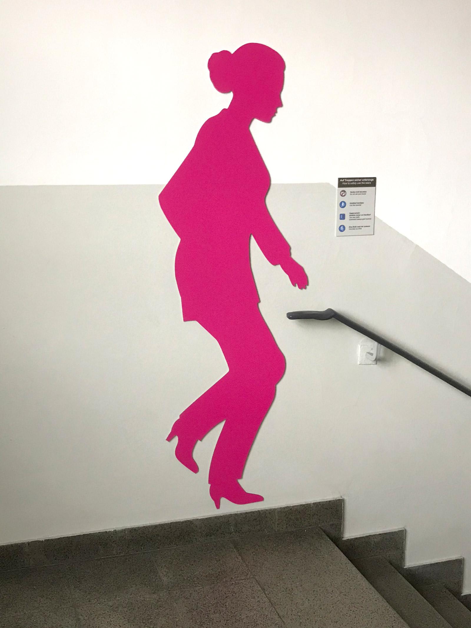 Pinke weibliche Schattenfigur in einem Treppenhaus an der Wand
