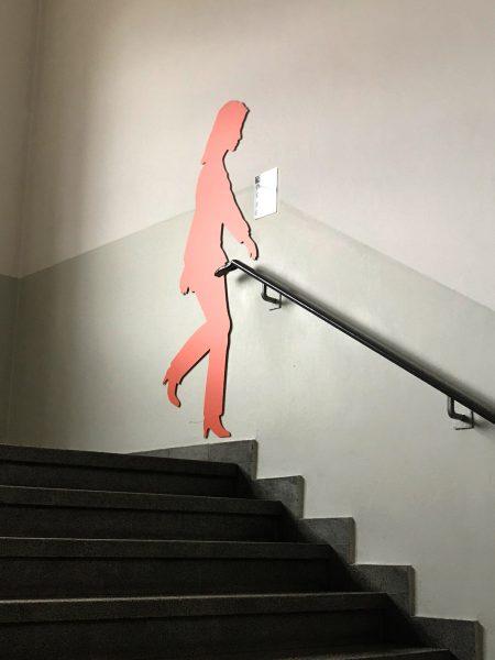 Orangefarbene weibliche Schattenfigur in einem Treppenhaus an der Wand