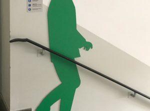 Schattenfiguren - Grüne männliche Schattenfigur in einem Treppenhaus an der Wand