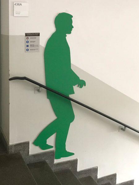 Grüne männliche Schattenfigur in einem Treppenhaus an der Wand