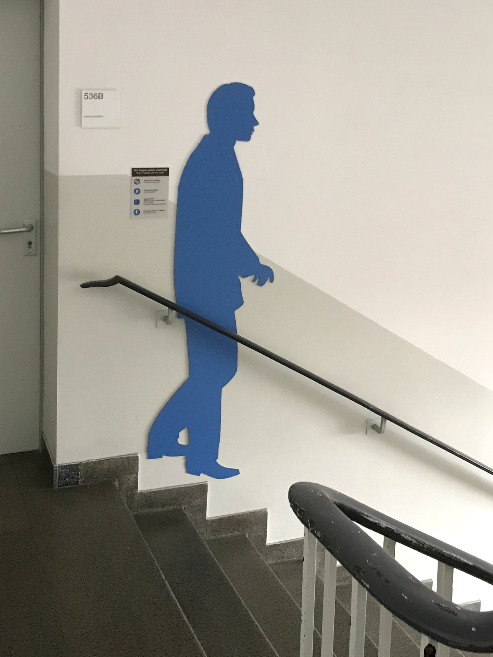 Blaue männliche Schattenfigur in einem Treppenhaus an der Wand