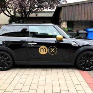 Fahrzeugfolierung - Seitenaufnahme von schwarzem Mini mit Logo in Goldfolie von moox