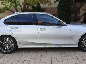 Seitenansicht eines silbernen BMWs mit einem kleinen Aufkleber von Brunner und Schmidt