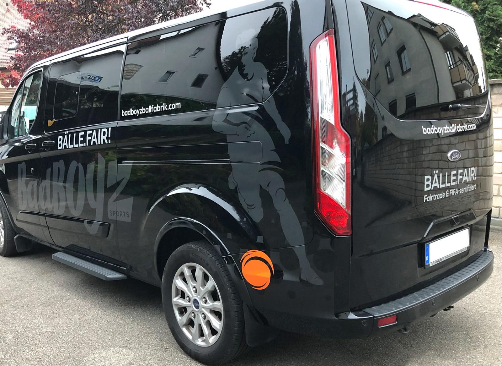 Seiten- und Heckansicht eines schwarzen Transporters mit einer neuen großflächigen Fahrzeugbeklebung von Badboyz Ballfabrik