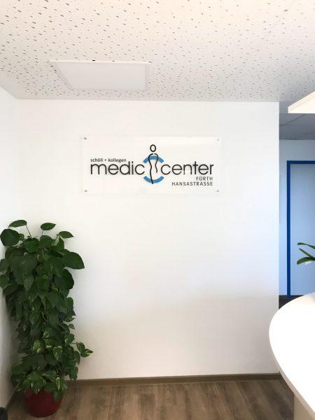 Plexiglasschild an Wand mit Medic Center Logo in einer der Arztpraxen