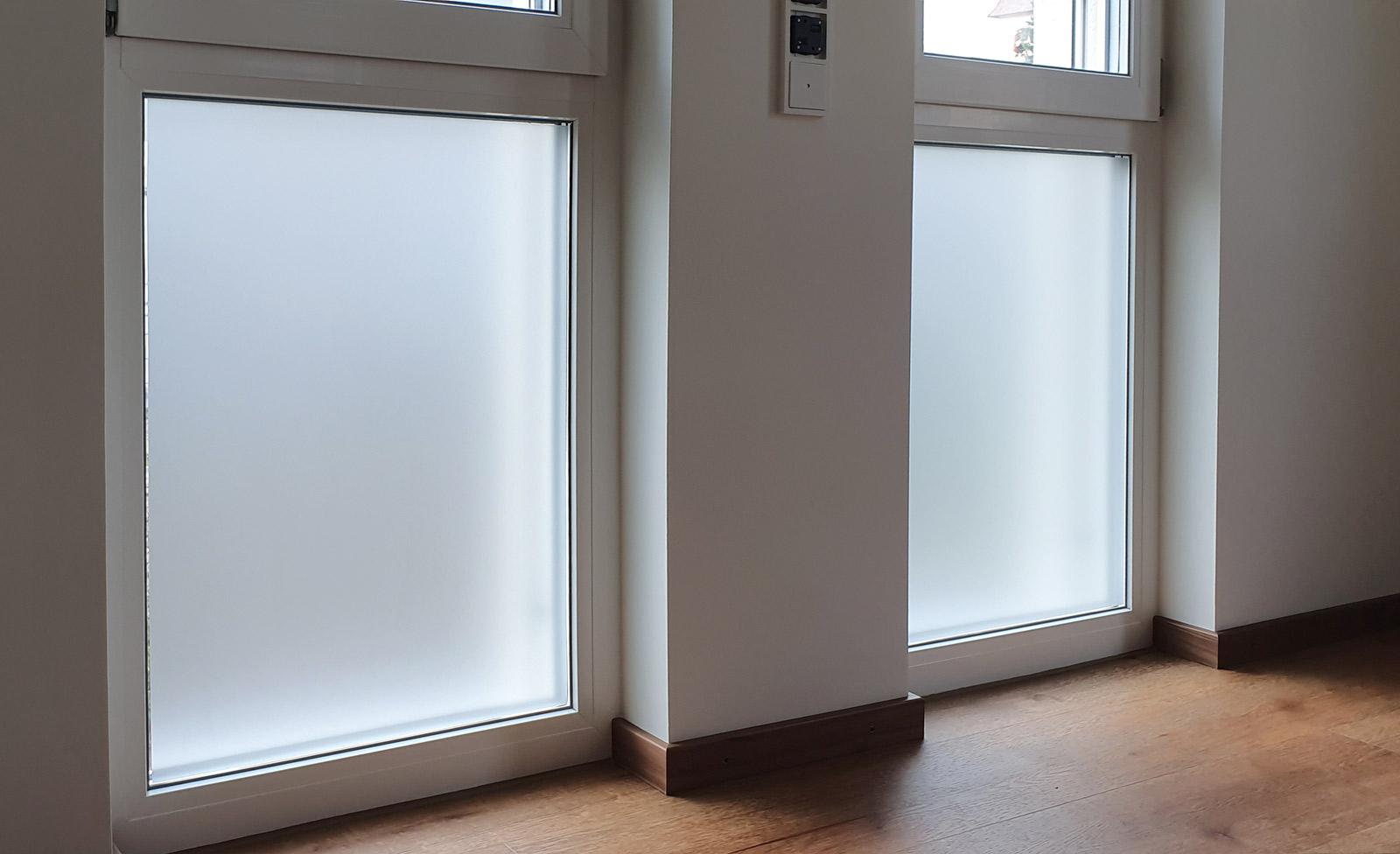 Zwei Fenster mit einer vollflächigen Sichtschutzfolierung aus Milchglasfolie
