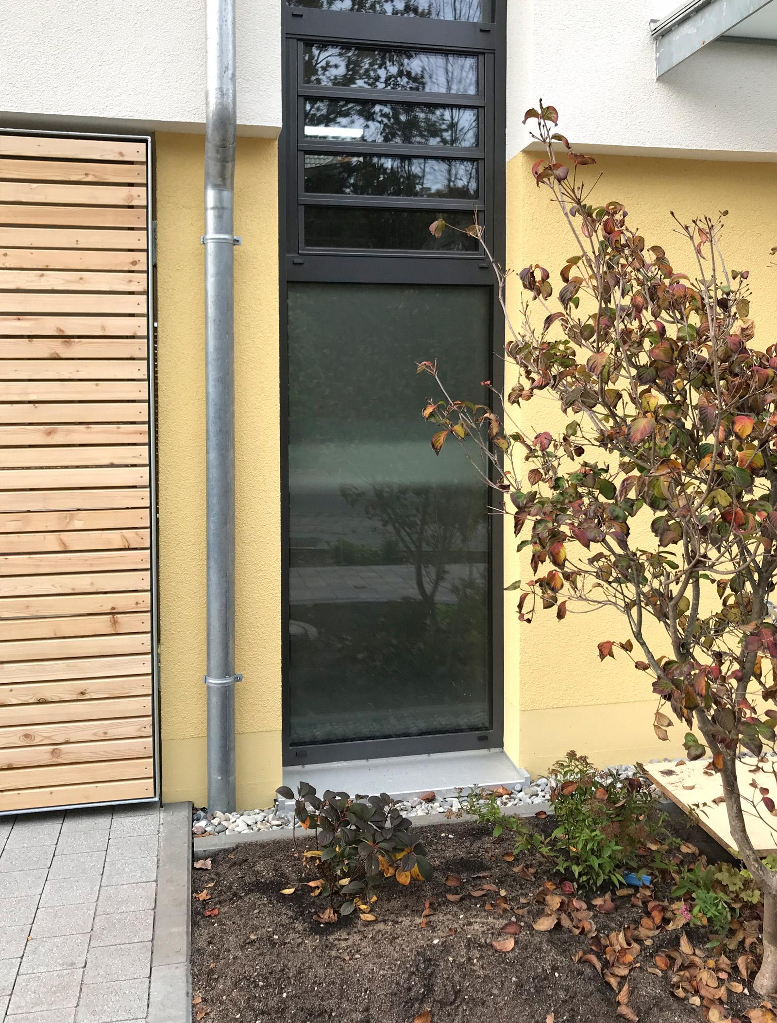 Hohes Fenster mit schwarzem Rahmen, dass von innen mit Glasdekorfolie beklebt ist und als Sichtschutz dient