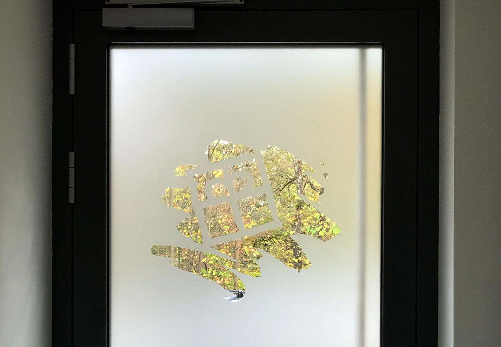 Auschnitt einer Hauseingangstüre von innen. Das Glas der Türe ist foliert mit negativ ausgeschnittenem Logo der Diakonie