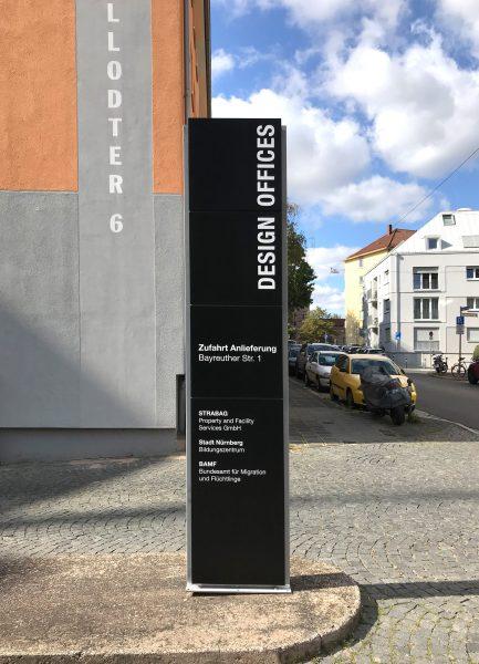 Hohe schwarze Stele mit weißer Folienbeschriftung von Design Offices