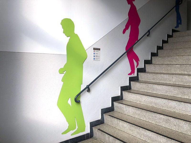 Drei Schattenfiguren in einem Treppenhaus. Jede Figur hat eine andere Farbe.