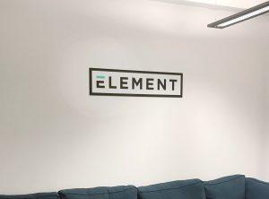 An einer weißen Wand hängt ein Alu-Dibond Schild mit dem Firmen Logo von Element