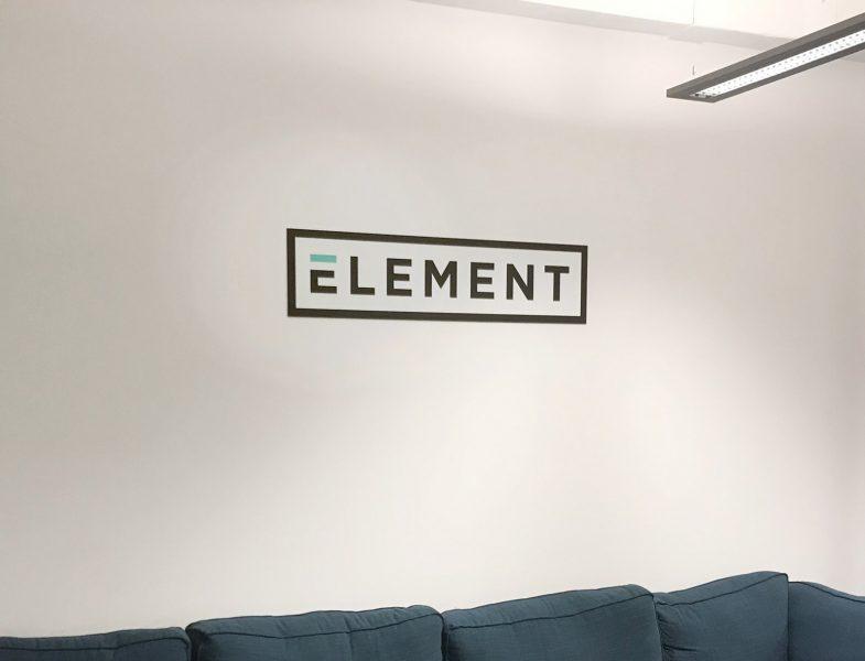 Beklebungsarbeiten - An einer weißen Wand hängt ein Alu-Dibond Schild mit dem Firmen Logo von Element