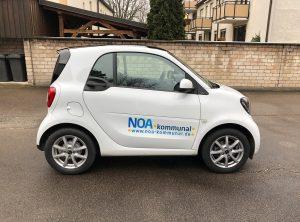 Fahrzeugbeklebung - Weißer Smart mit einem NOA kommunal Logo an der Seite