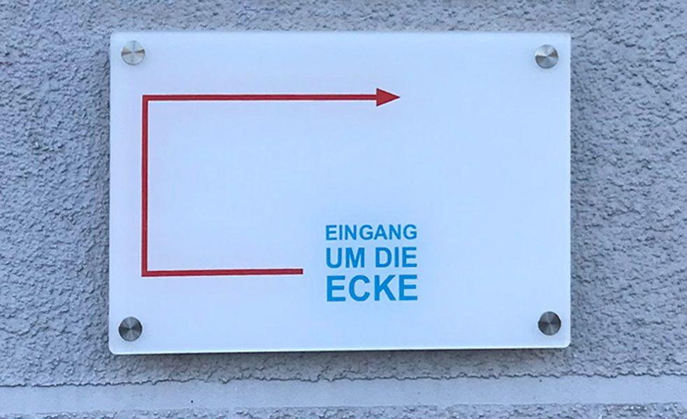 Kleines weißes Plexiglasschild das mit Edelstahlabstandshaltern an einer grauen Hauswand hängt. Darauf ist ein roter Pfeil abgebildet und ein Text mit den Worten Eingang um die Ecke