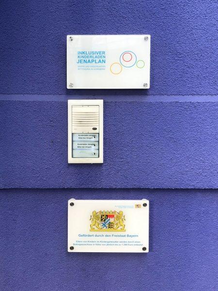 Beklebung - Weiße Plexiglasschilder die mit Edelstahlabstandshaltern an einer lilanen Hauswand hängen und mit entsprechenden Beschriftungen foliert wurden
