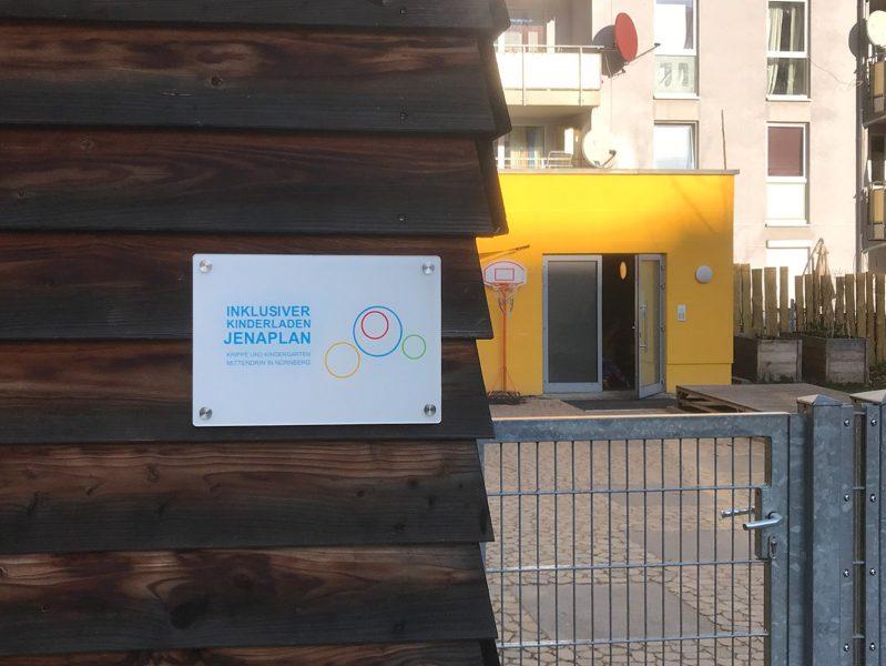 Weißes Plexiglasschild das mit Edelstahlabstandshaltern an einer Holzbrettwand hängt und mit entsprechenden Beschriftungen foliert wurde