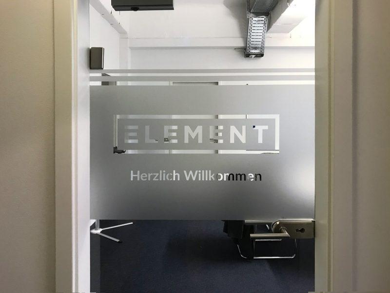 Beklebungsarbeiten - Glastür mit negativ ausgeschnittenem Logo aus einer darauf angebrachten Milchglasfolie