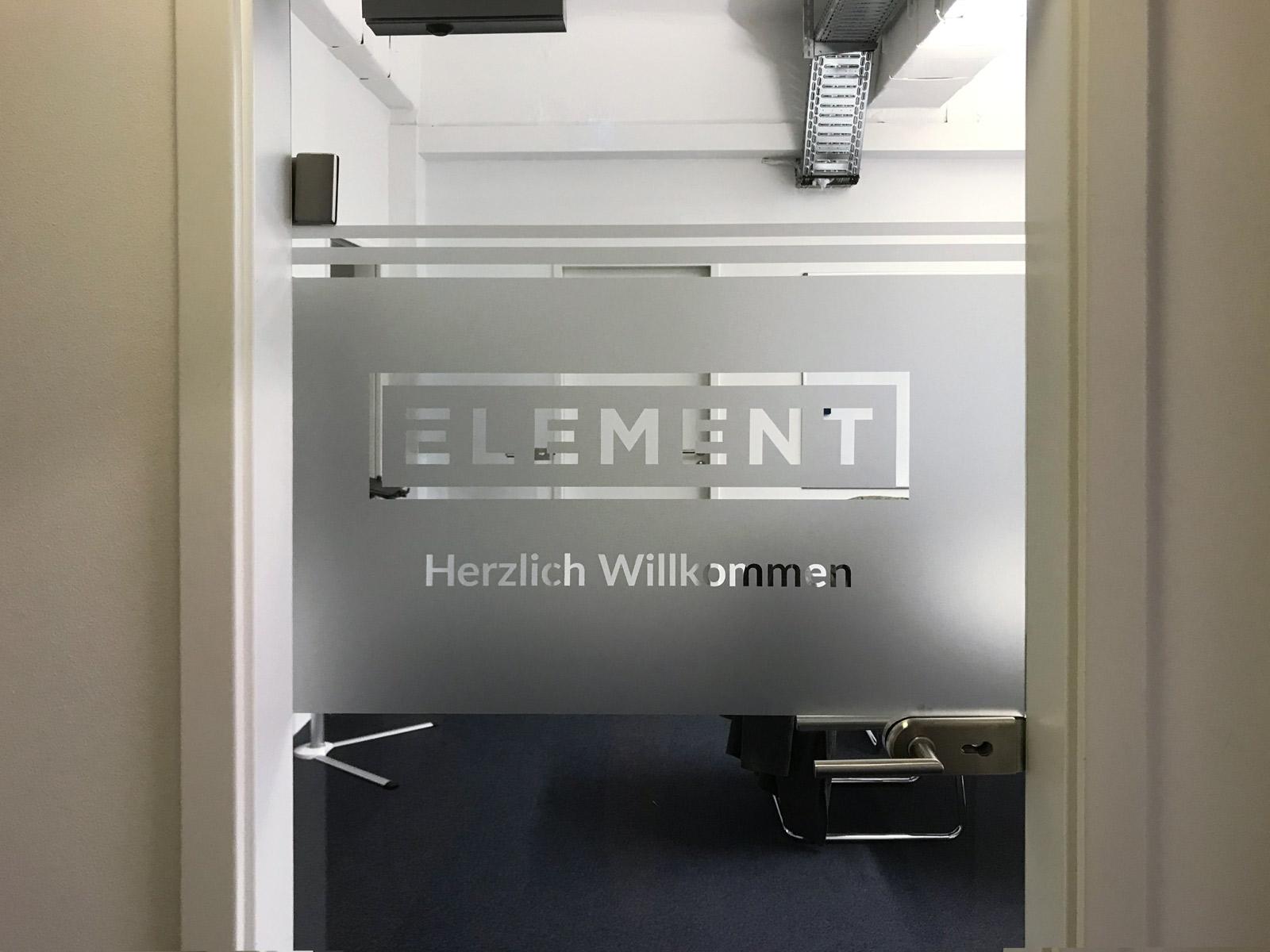 Glastür mit negativ ausgeschnittenem Logo aus einer darauf angebrachten Milchglasfolie