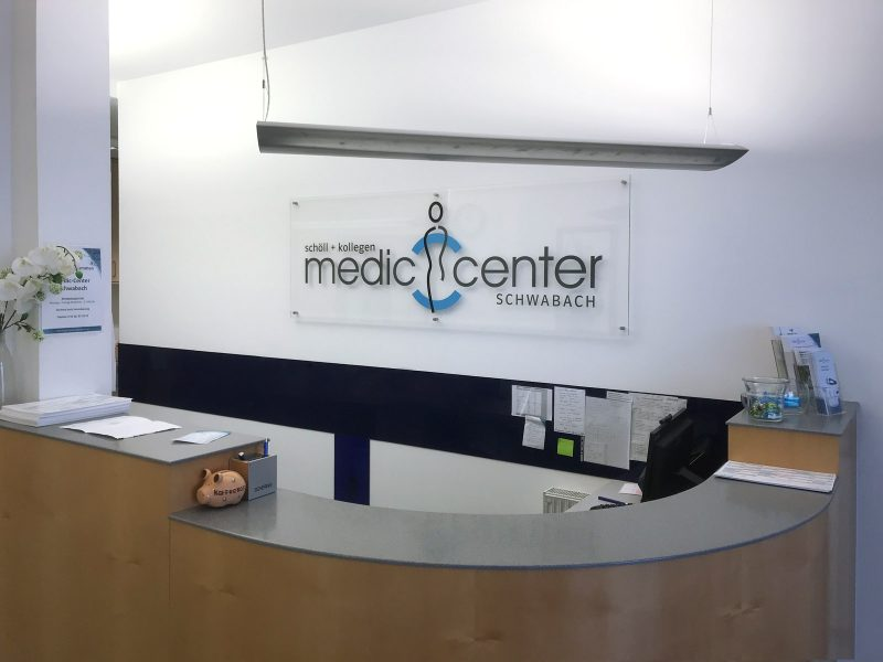Transparentes Acrylschild mit dem Logo vom Medic Center an einer weißen Wand hinter dem Empfang