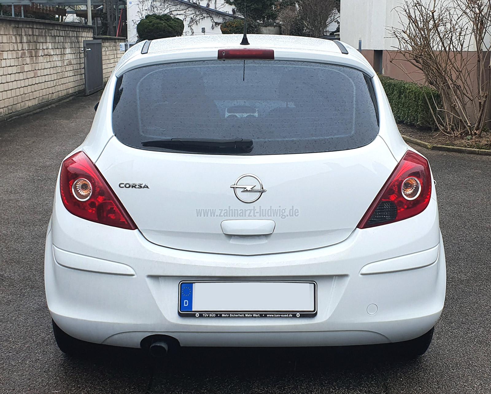 Weißer Opel Corsa mit dezenter Heckbeklebung von Zahnarzt Ludwig