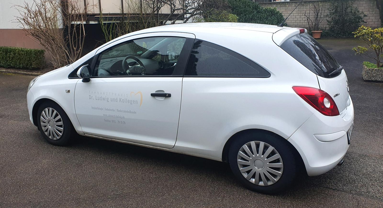 Weißer Opel Corsa mit dezenter Beklebung an der Seite von Zahnarzt Ludwig