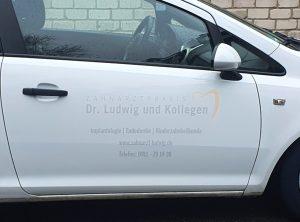 Weiße Opel Corsa Türe mit dezenter Folienbeschriftung von Zahnarzt Ludwig