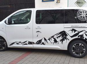Fahrzeugbeklebung - Seitenansicht eines weißen Fahrzeuges mit Aufklebern im Alpendesign