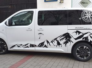 Seitenansicht eines weißen Fahrzeuges mit Aufklebern im Alpendesign