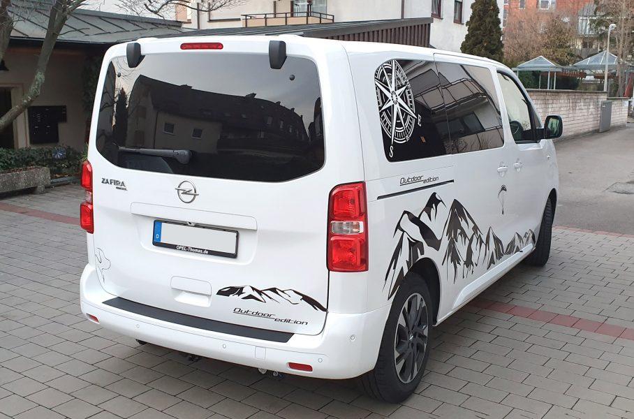Seiten- und Heckansicht eines weißen Opel Zafiras mit Aufklebern im Alpendesign
