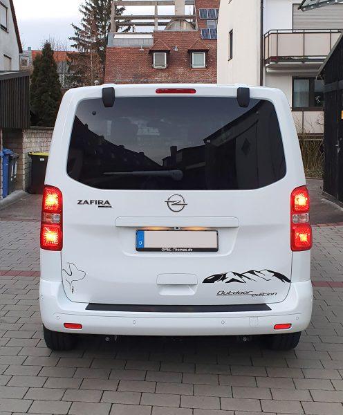 Heckansicht eines weißen Opel Zafiras mit Aufkleber im Alpendesign