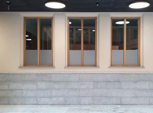 Sichtschutzbeklebung - Hohe Fenster mit Holzrahmen, die etwa ein drittel mit Glasdekorfolie abgedeckt sind