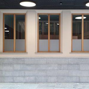 Hohe Fenster mit Holzrahmen, die etwa ein drittel mit Glasdekorfolie abgedeckt sind